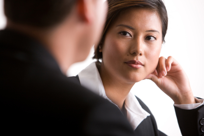 Woman leaning her face on her hand and listening to her co-worker